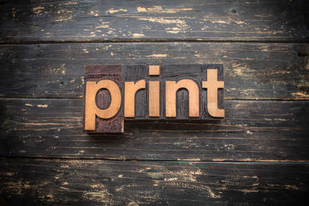 """The word """"PRINT"""" written in vintage wood letterpress type on a vintage rustic background."""