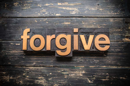"""The word """"FORGIVE"""" written in vintage wood letterpress type on a vintage rustic background."""