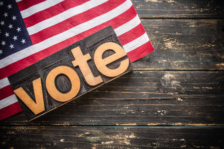 "The word ""VOTE"" written in vintage wood letterpress type on a vintage rustic background."