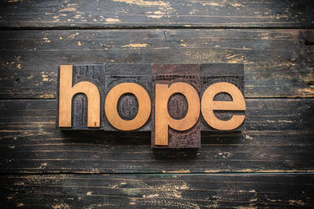 """The word """"HOPE"""" written in vintage wood letterpress type on a vintage rustic background."""
