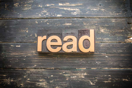 "The word ""READ"" written in vintage wood letterpress type on a vintage rustic background."