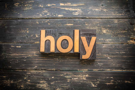 """The word """"HOLY"""" written in vintage wood letterpress type on a vintage rustic background."""