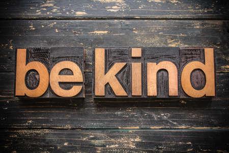 "The words ""BE KIND"" written in vintage wood letterpress type on a vintage rustic background. Standard-Bild"