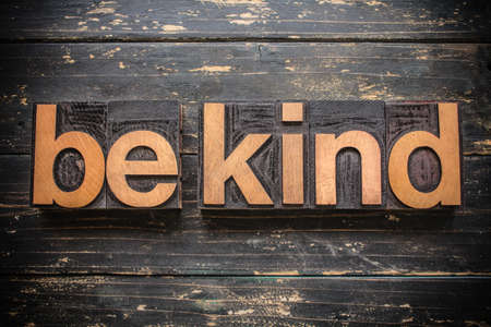 """The words """"BE KIND"""" written in vintage wood letterpress type on a vintage rustic background. Imagens"""