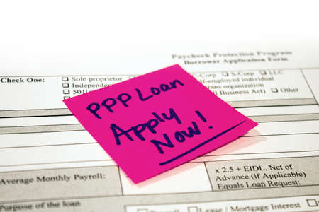 An application for the Paycheck Protection Program with a reminder note stuck to it.