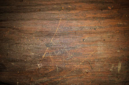 An old scratched and worn brown wood background.