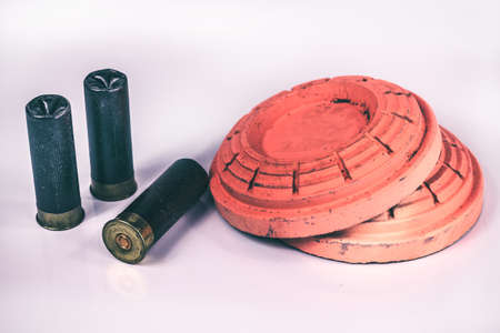 A pair of orange skeet and trap shooting clay targets with shotgun shells isolated on a white background.