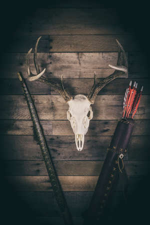 A traditional archery hunting scene with bow, quiver of arrows, and buck antlers.