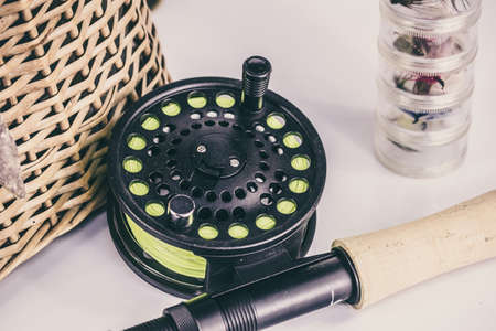 A fly fishing rod and reel with a fisherman's creel and flies.