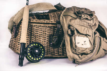 A fly fishing rod and reel, vest, and fishing creel isolated on a white background. 免版税图像
