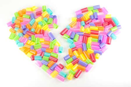 rainbow cocktail: Colored potabile cannucce a forma di cuore su uno sfondo bianco