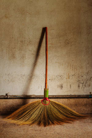 besom: Old obsolete broom or besom leaning on the gray wall Stock Photo