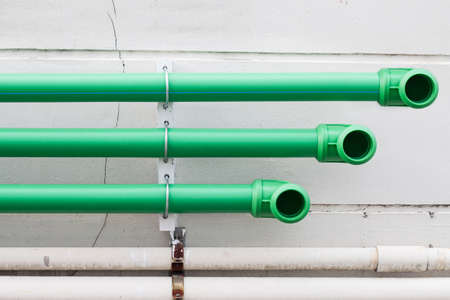 plastic conduit: green plastic pipes on the cement wall