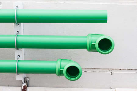 plumbing supply: green plastic pipes on the cement wall
