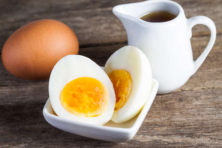 boiled eggs: boiled eggs in small plate with sauce on the wood table