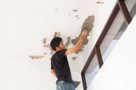 Plasterer at indoor at ceiling renovation decoration Stock Photo