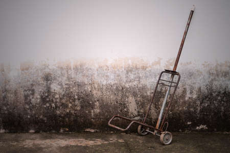 hand truck: steel hand trolley or sack truck against old brick wall Stock Photo