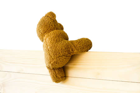 Teddy bear climbing the wood wall isolated on white background with clipping path
