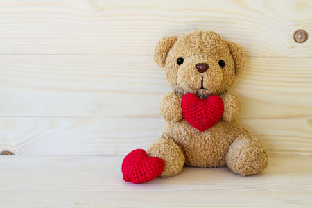 Teddy bear holding a heart-shaped pillow on wood board background