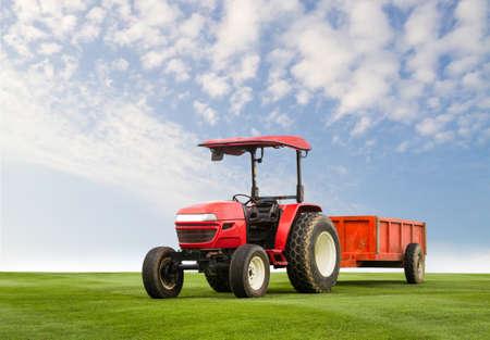 arando: Tractor rojo con remolque en un campo de hierba