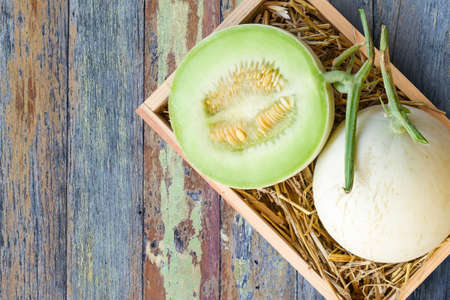 Green cantaloupe melon in wood box on wood background