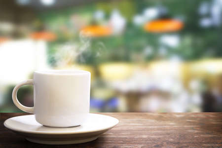 white coffee cup with steam on the wooden shelf on coffee shop background