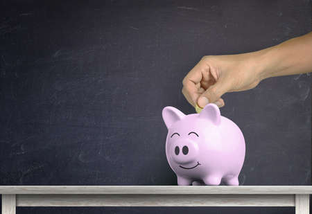 human hand dropping a coin into white piggy bank on wood shelf with against chalkboard background Imagens - 150706683