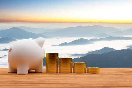 Piggy bank and a pile of coins on old wooden desk with beautiful sunrise background, Saving money for travel concept.3d render