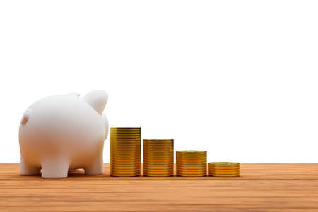 Piggy bank and a pile of coins on old wooden desk isolated on white  background