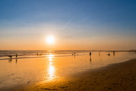 People bathing in the sun in sunset, swiming and playing games on the beach. Tourists on the sand beach in Bali, Indonesia Stock Photo