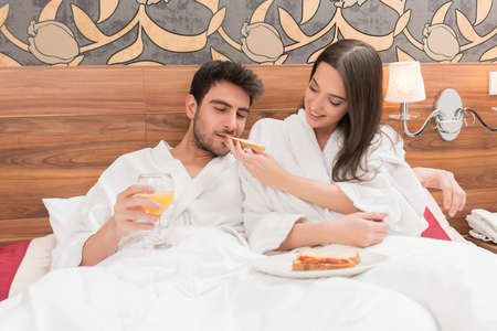 Attractive young couple in white robes, enjoying food and drink in bad after spa.Couple in relationship love and care Banque d'images - 101989414