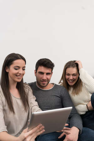 Group of friends two couples sitting on sofa and taking selfie with tablet Stock Photo