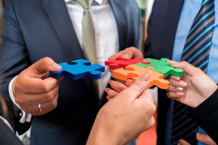 Mensen uit het bedrijfsleven puzzel oplossen. Team kleurrijke puzzelstukjes in handen houden
