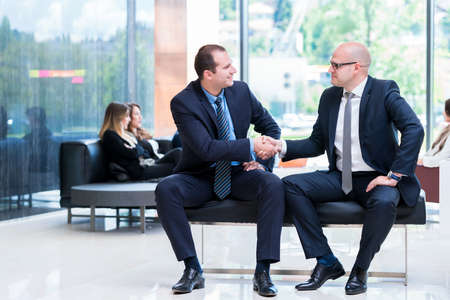 Business partners handshaking after signing contract. Stock Photo