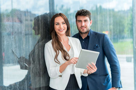 Businesspeople With Digital Tablet standing In Modern Office