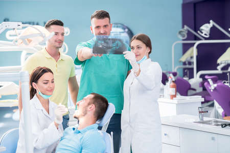 Dental medical team examining and working on young male patient.Dentists office, while technician is reviewing xray.