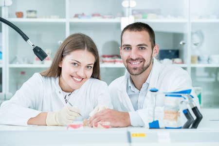 Giovane squadra di odontotecnici che fanno protesi dentarie. Processo di fabbricazione della protesi.