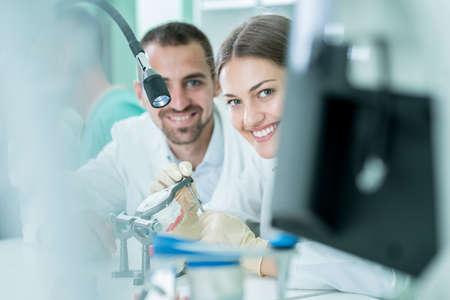 Giovane squadra di odontotecnici che fanno protesi dentarie. Processo di fabbricazione della protesi. Archivio Fotografico