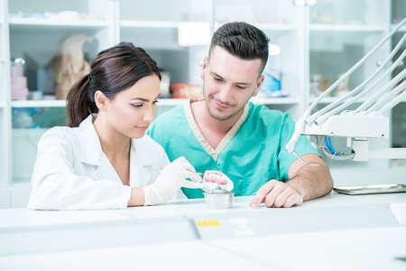Giovane squadra di odontotecnici che realizzano protesi dentali. Processo di fabbricazione della protesi. Archivio Fotografico