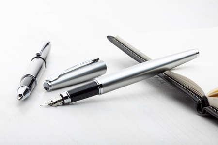 ball pens stationery: Pluma de plata y pluma del rodillo con el cuaderno de cuero en el fondo blanco