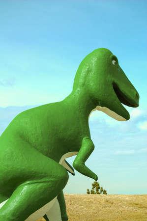 A big green dinosaur walking through the land.