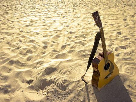 An acoustic guitar standing in the sandy beach. Banco de Imagens