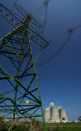 Tall green electricity pylon with power plant in background Stockfoto