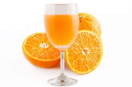 extracting: a glass of orange juice is on center of frame with orange fruit