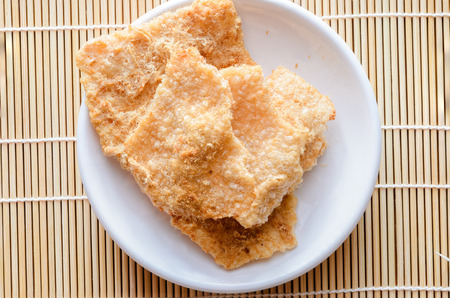 shred: rice cracker top up dried shred pork on white plate Stock Photo