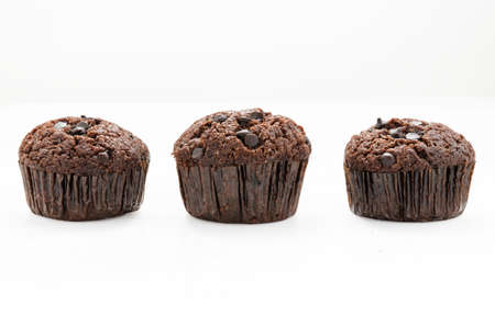 abreast: Three abreast of chocolate muffins on white background with clipping path