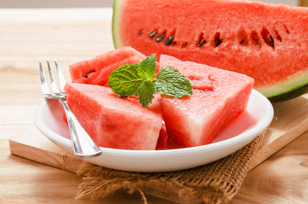 close up watermelon and peppermint on white plate