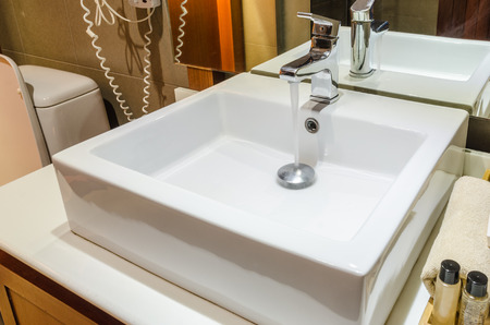 amenities: Washbasin and faucet in bathroom with amenities and towels