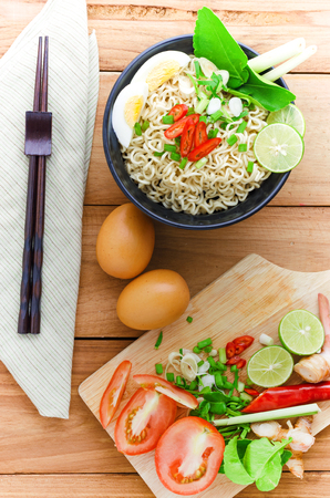 cooked instant noodle: An instant noodle in black bowl cooked spicy taste with some ingredients and choppingstick and eggs put beside.