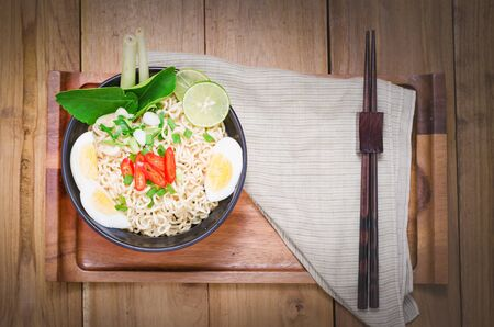 cooked instant noodle: instant noodle on black bowl cooked spicy taste put on wooden table beside with chopsticks